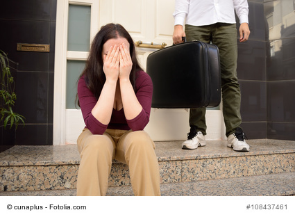 woman expelled of home sitting and weeping and the wife holding the suitcase of husband in background at the doorway as concept of divorce
